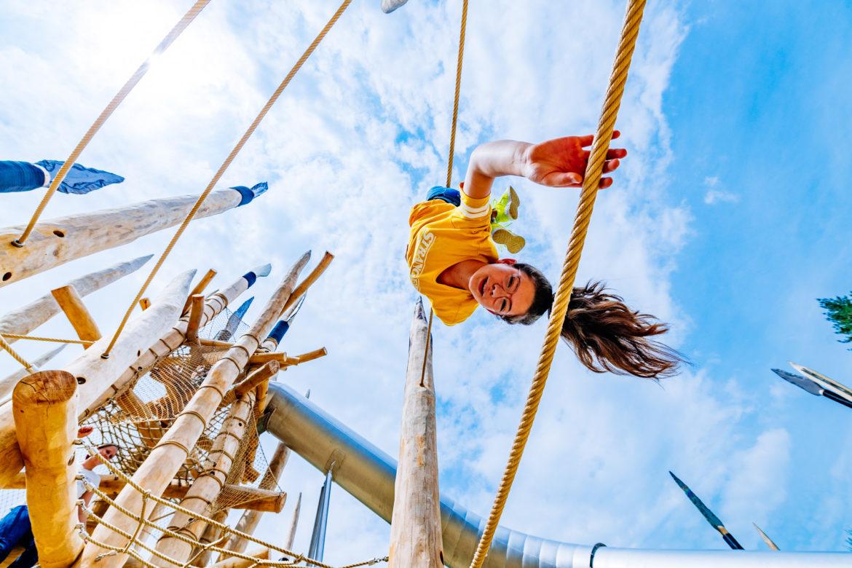 Mädchen hängt kopfüber am Seil auf dem Steinzeitspielplatz