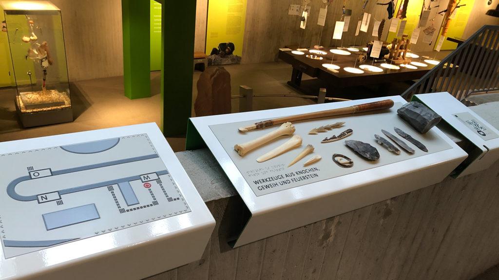 Drei Tastobjekte in der Dauerausstellung: Eine Orientierungskarte, Werkzeuge aus Knochen, Geweih und Feuerstein sowie die QR-Code-Station für das Mobile Game