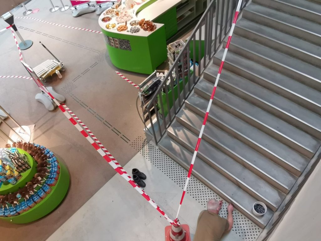 Ein Mann bringt kleine Elemente des Bodenleitsystems am Treppenaufgang zur Dauerausstellung an