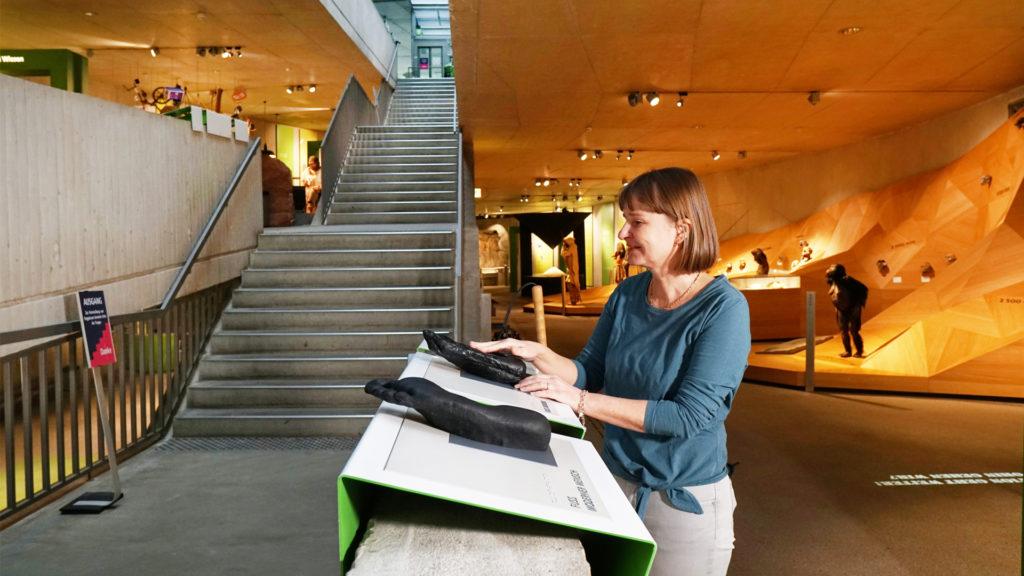 Tamara Ströter steht an der Taststation mit detaillierten Fußrepliken.