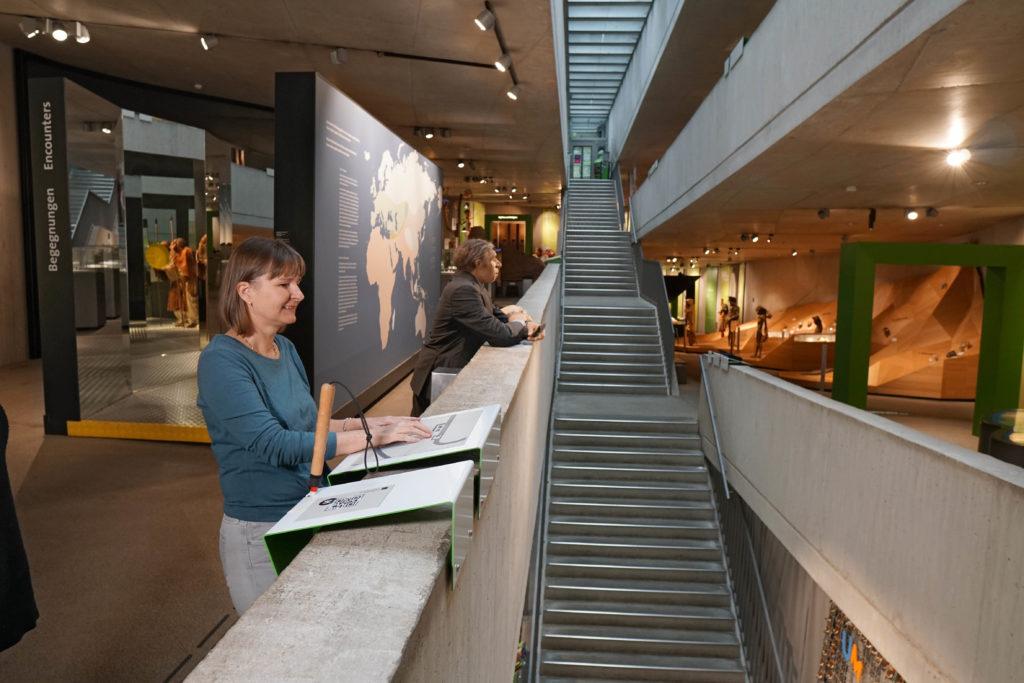 Tamara Ströter steht an einem Tastobjekt. Neben ihr lehnt unsere Neanderthaler Dermoplastik Mr 4% an der Treppenbrüstung.