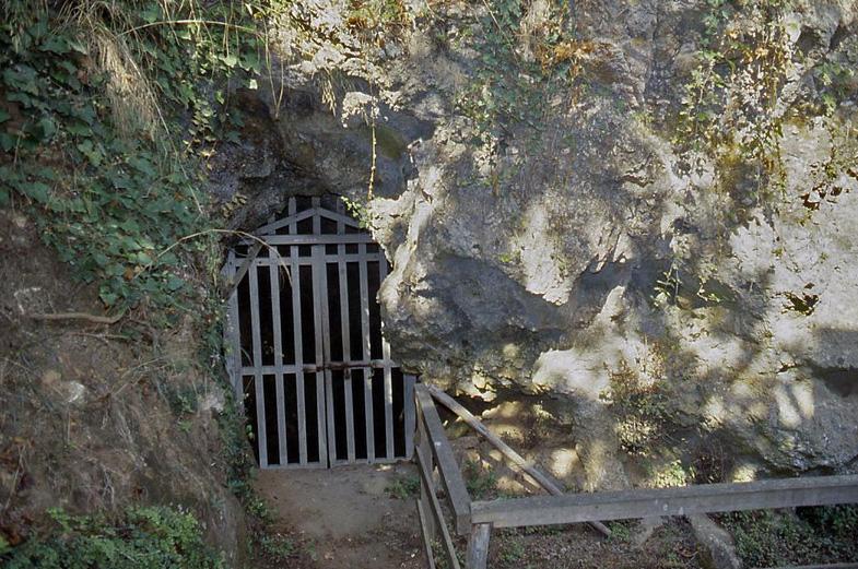 Eine große Felswand in der sich ein kleiner Eingang befindet, der zur Höhle führt. Der Eingang ist mit einem Tor verschlossen.