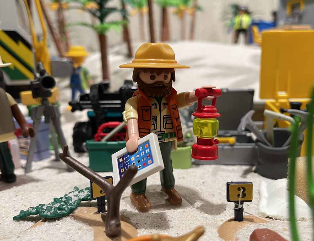 Ein PLAYMOBIL-Archäologe steht auf dem Sandboden einer Vitrine und hält seine Lampe sowie ein Notebook in den Händen. Um ihn herum stehen mehrere Geräte und Artefakte.