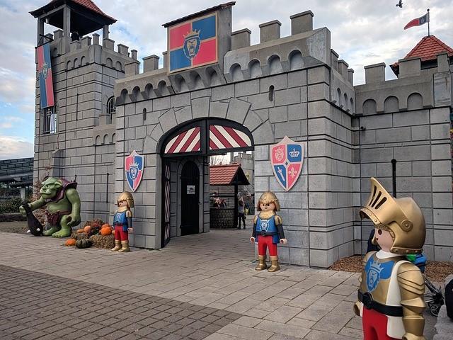 Eine große, lebensechte Burg vor der mehrere lebensgroße PLAYMOBIL-Ritter stehen.