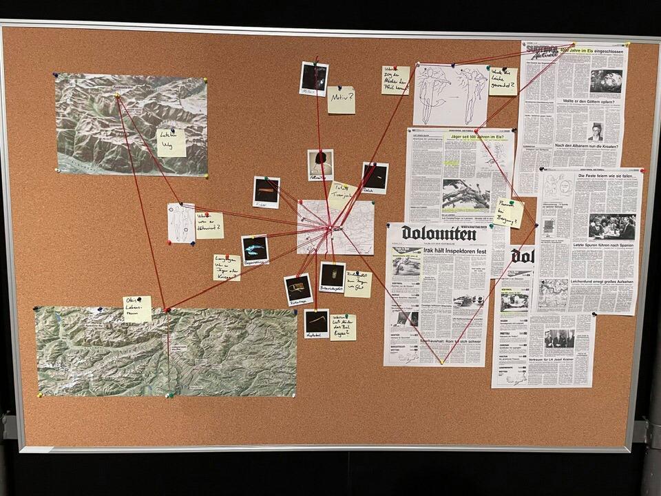 Eine Kork-Pinnwand auf der verschiedene Beweisstücke zu einer Übersichts-Karte des Tatortes zusammengefasst sind.