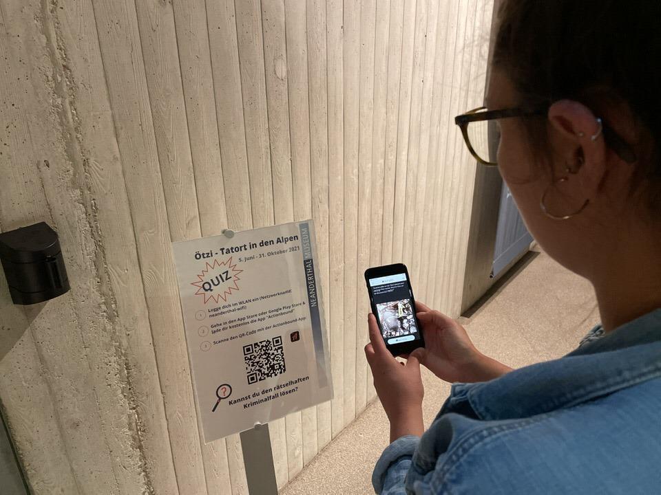 Eine Frau scannt einen QR-Code auf einem Poster am Eingang der Sonderausstellung.