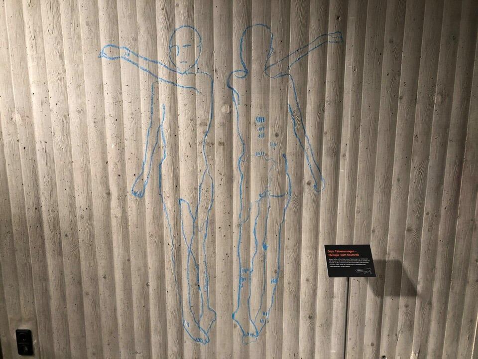 An die Wand der Sonderausstellung sind mit Kreide die Umrisse der Ötzi-Mumie gezeichnet. Auf dem Körper wurden mit Strichen die Tattoos markiert.