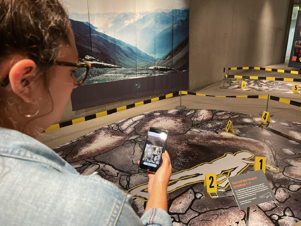 Eine Frau macht mit ihrem Smartphone ein Foto vom rekonstruierten Tatort in der Sonderausstellung