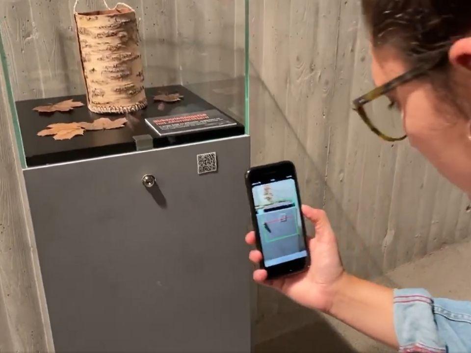Ein Frau scannt einen QR-Code, der sich auf einer Glasvitrine befindet. In der Vitrine sieht man einen Behälter, den Ötzi bei sich getragen hat.