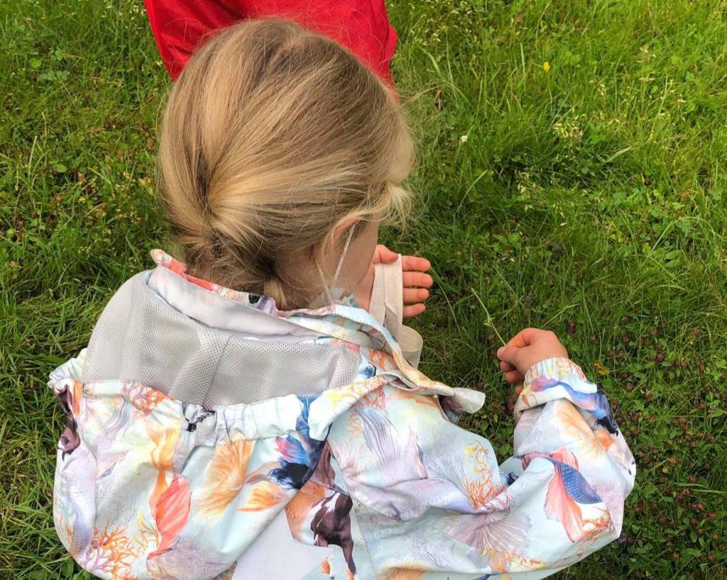 Das Mädchen wird von hinten gezeigt wie sie kniend einen Grashalm auf der Wiese pflückt.