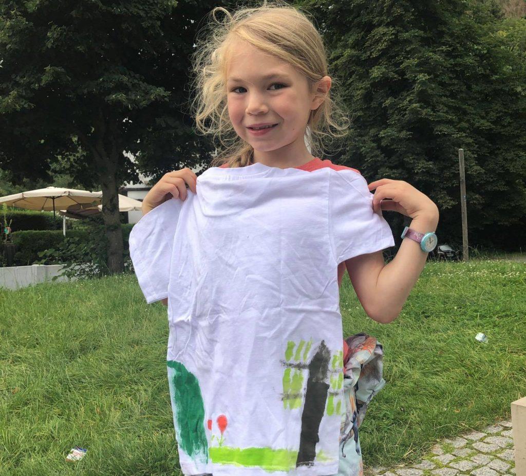 Das Mädchen steht und hält sich ein T-Shirt vor die Brust. Das T-Shirt wurde mit einem Baum, einer Wiese und Blumen bemalt bzw. bedruckt.