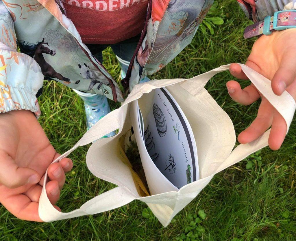 Lara steht auf einer grünen Wiese und hält ihre geöffnete kleine Tasche in die Kamera. In dem Täschchen sind das Heft, Haselnüsse und Blätter.