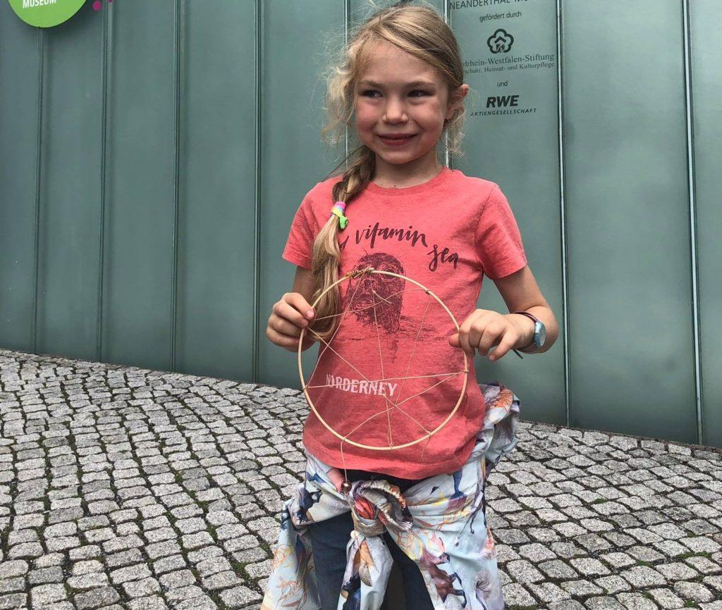Das Mädchen steht vor dem Eingang des Neanderthal Museums und zeigt ihren fertigen, gebastelten Traumfänger.