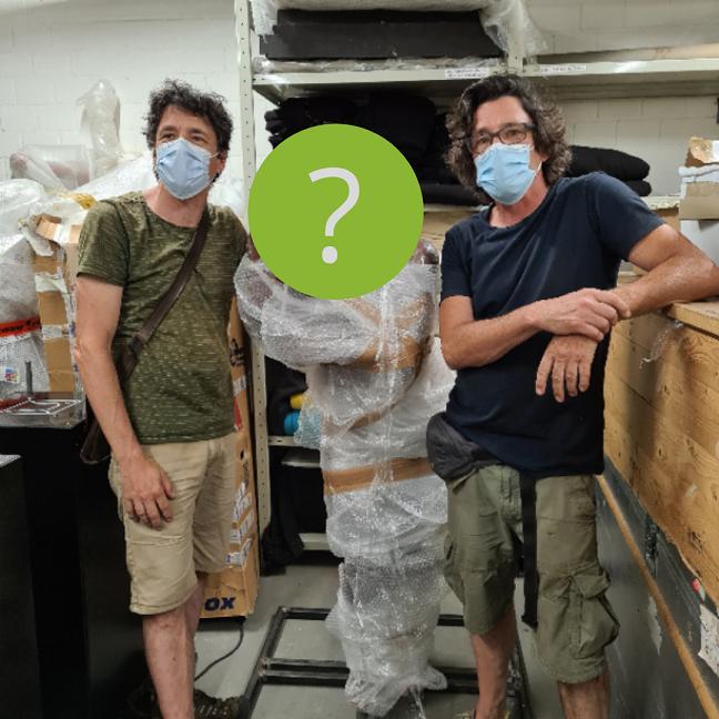 Die zwei Künstler Adrie und Alfons Kennis stehen etspannt neben der von ihnen gebauten, neuen Konstruktion des Mr. N. Dieser ist eingepackt in Folie, sein Gesicht durch einen grünen Störer verdeckt, sodass er nicht erkannt wird.