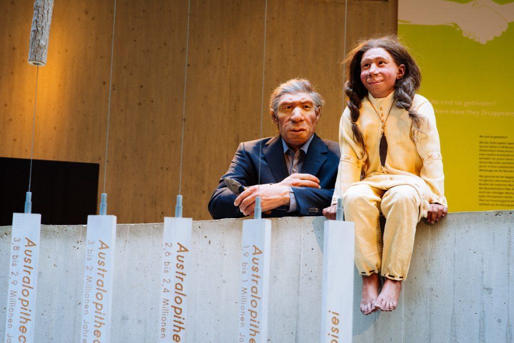 Die Konstruktion von Mr. 4% steht im Anzug an der Brüstung in der Ausstellung. Neben ihm sitzt Kina lächelnd auf dem Betonvorsprung. Im Vorder- und Hintergrund sieht man Teile von Ausstellungstexten.