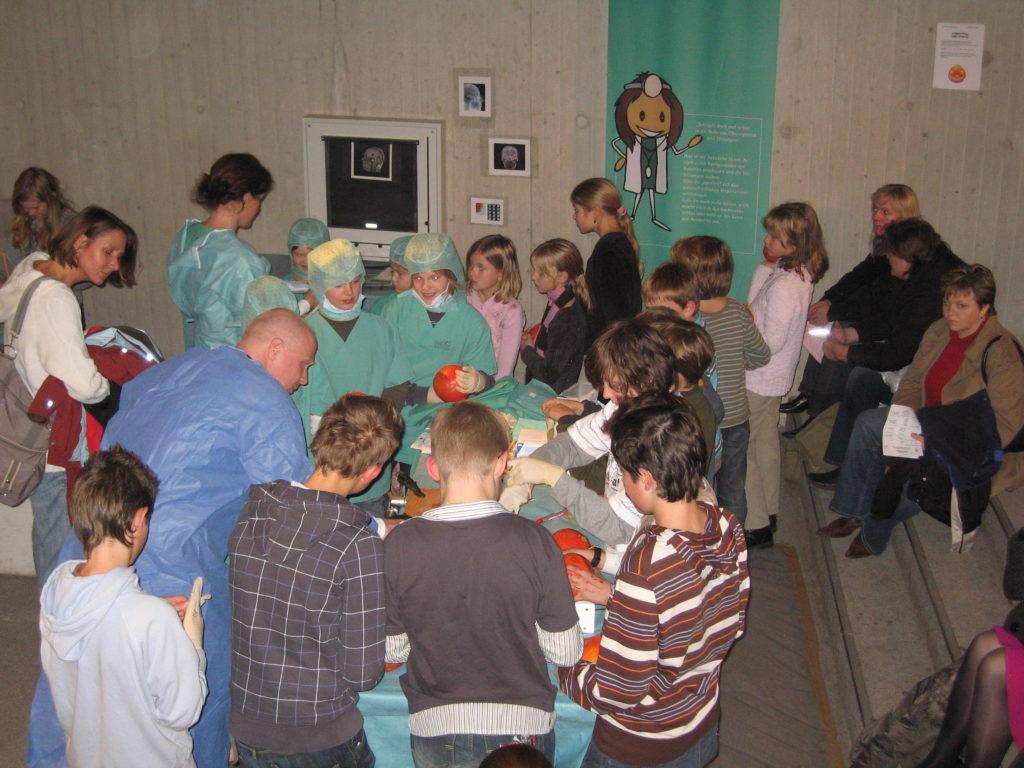 Prof. Michael Sabel und einige Kinder in OP-Mänteln und Hauben stehen um einen OP-Tisch in der Ausstellung und bearbeiten Kürbisse.
