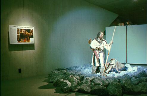 Blick in die erste Ötzi-Sonderausstellung. Ötzi-rekonstruktion steht auf Steinen und wir beleuchtet, ebenso die Erklärtafel links neben ihm an der Wand.