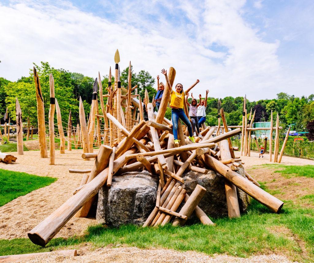 Blick auf die Höhle und den Pfahllanzenturm auf dem Steinzeitspielplatz mit spielenden Kindern.